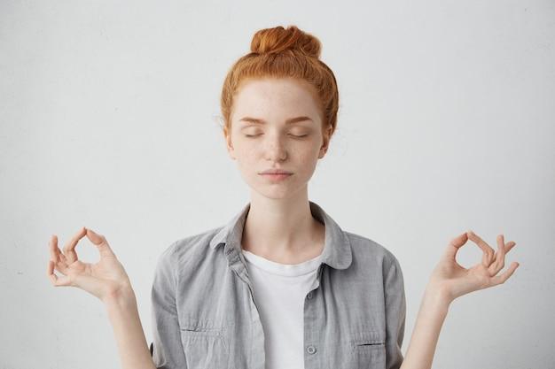 Ludzie, joga i koncepcja zdrowego stylu życia. portret pięknej młodej rudowłosej kobiety z zamkniętymi oczami podczas medytacji w pomieszczeniu, ćwicząc spokój umysłu, trzymając palce w geście mudry