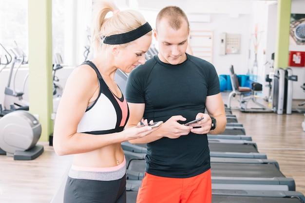 Ludzie korzystający z telefonów na siłowni
