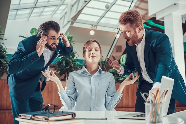 Ludzie krzyczą na medytującego pracownika w biurze.