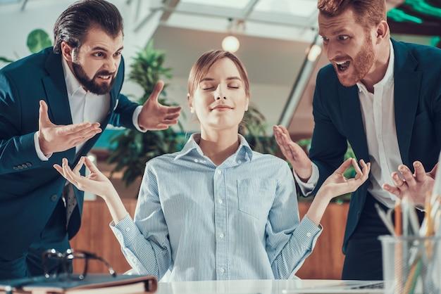 Ludzie krzyczą na medytującego pracownika w garniturze w biurze.