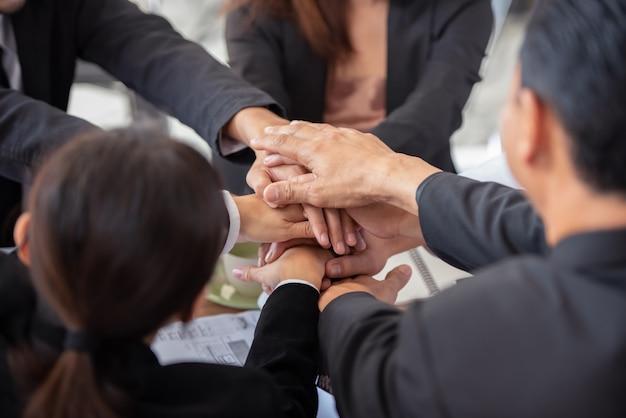 Ludzie łączący ręce demonstrują pracę zespołową.