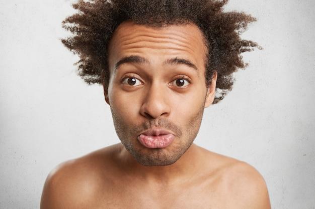 Ludzie, ludzkie wyrażenia i koncepcja uczuć. zabawny ciemnoskóry mężczyzna z fryzurą afro oszukuje sam