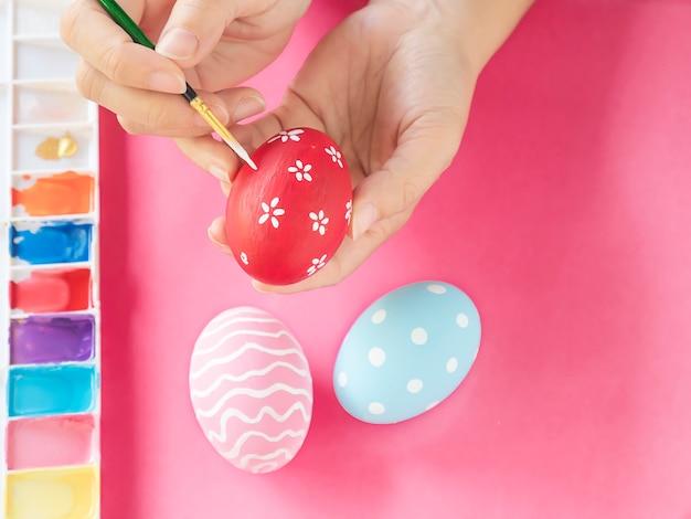 Ludzie maluje kolorowych wielkanocnych jajek - wielkanocny wakacyjny świętowania pojęcie