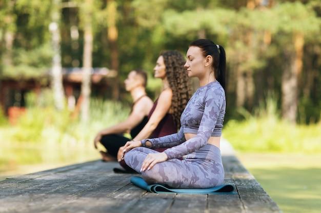 Ludzie medytują siedząc na macie w pozycji lotosu na drewnianym moście w parku