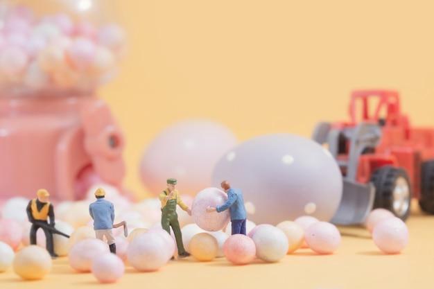 Ludzie (miniaturowe) przygotowują święta wielkanocne na tle automatu sprzedającego jaja.