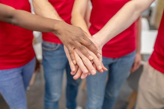 Ludzie myślący podobnie. ręce czterech wolontariuszy w dżinsach i czerwonych koszulkach w uścisku dłoni ukazujące jedność