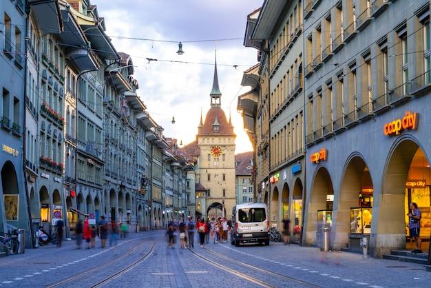 Ludzie na alei handlowej z wieżą zegarową astronomiczną zytglogge w bernie w szwajcarii