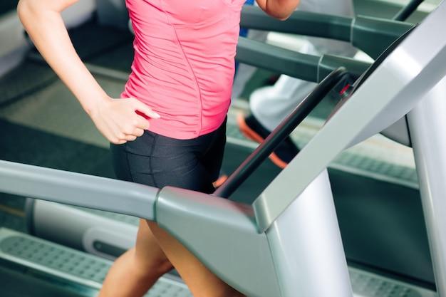 Ludzie na bieżni w siłowni działa