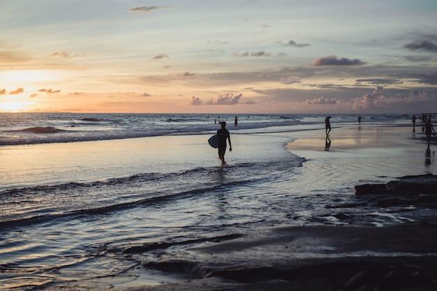Ludzie na brzegu oceanu o zachodzie słońca.