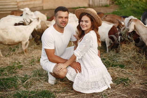 Ludzie na farmie. para z kozami. kobieta w białej sukni.