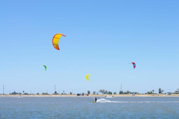 Ludzie na jeziorze uprawiają kitesurfing