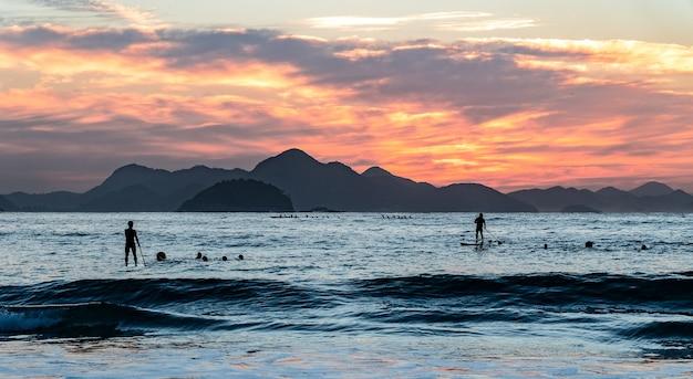 Ludzie na łodziach na morzu z sylwetkami wzgórz podczas zachodu słońca na