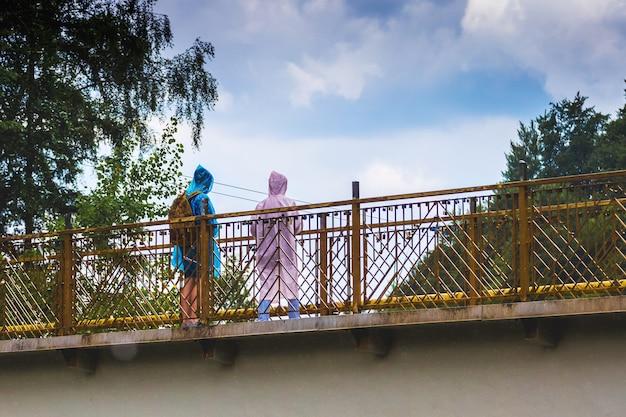 Ludzie na moście w płaszczach przeciwdeszczowych chowają się przed deszczem