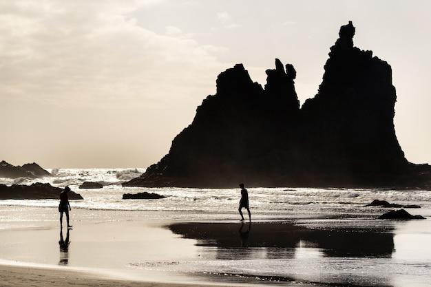 Ludzie na piaszczystej plaży benijo na teneryfie w hiszpanii.