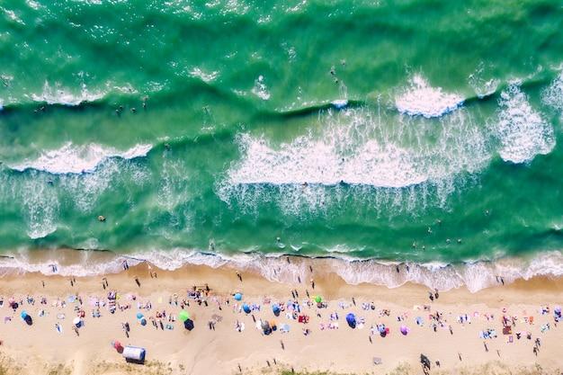 Ludzie na plaży i ludzie pływający w morzu