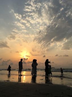 Ludzie na plaży o zachodzie słońca zabawy