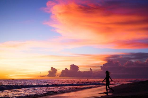 Ludzie na plaży o zachodzie słońca.