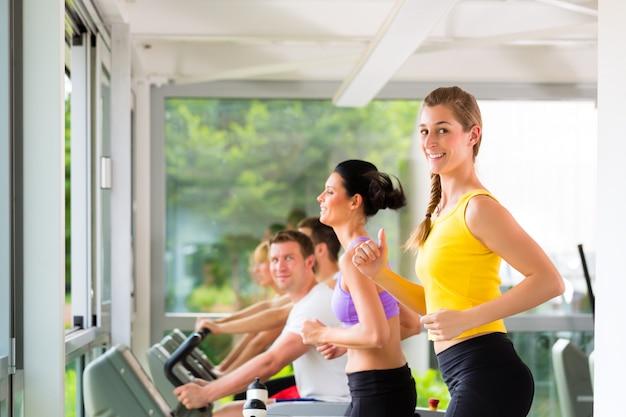 Ludzie na siłowni sportowej na bieżni
