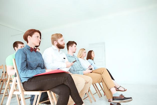 Ludzie na spotkaniu biznesowym w pustej sali konferencyjnej.