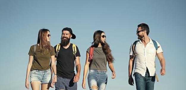 Ludzie na wakacjach podróżują piesze wycieczki mężczyźni i kobiety podróżują na letnie wakacje szczęśliwi przyjaciele na błękitnym niebie wanderlust przyjaźń przyjaciele młodzi ludzie styl życia