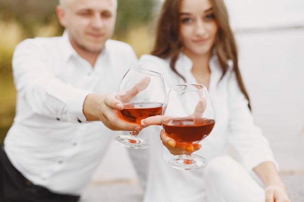 Ludzie nad rzeką. pyszny, zdrowy letni piknik na trawie. czerwona winorośl.