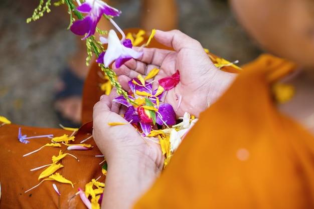 Ludzie nalewa wodę mnichom buddyjskim i daje błogosławieństwo w tajlandii songkran coroczny festiwal w buddyjskiej świątyni