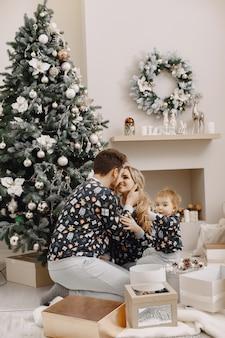 Ludzie naprawiający na święta. ludzie bawią się z dzieckiem. rodzina odpoczywa w świątecznym pokoju.