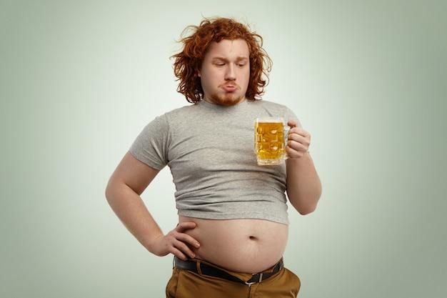 Ludzie, niezdrowy tryb życia, otyłość i obżarstwo. otyły, gruby, młody europejczyk z kręconymi rudymi włosami trzymający szklankę piwa, wahający się przed podjęciem decyzji o wypiciu go po dobrym obiedzie