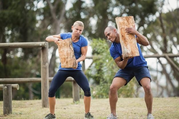 Ludzie niosący ciężkie drewniane kłody podczas toru przeszkód w obozie treningowym