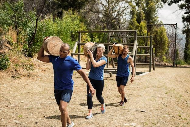Ludzie niosący ciężkie drewniane kłody podczas toru przeszkód