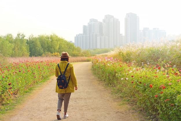 Ludzie noszą żółtą kurtkę spacerując po pięknym parku do budynków