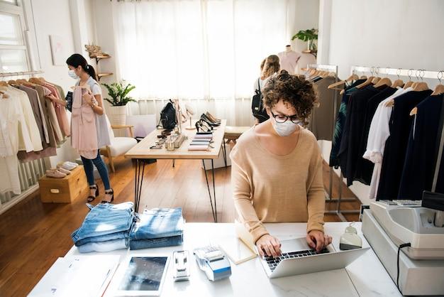 Ludzie noszący maski w sklepie odzieżowym robią zakupy w nowej normalności