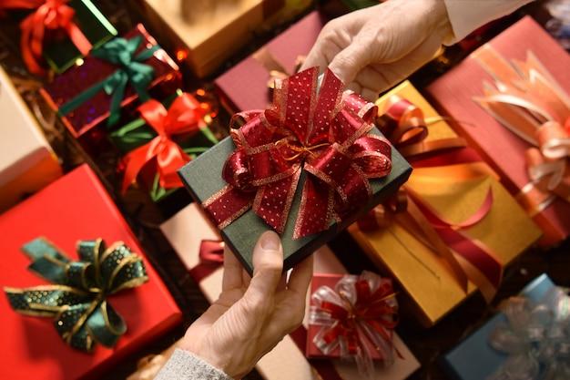 Ludzie obdarowujący się nawzajem podczas świąt bożego narodzenia i nowego roku z pudełkami prezentów w