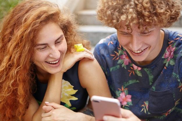 Ludzie oglądający komedię na smartfonie, odpoczywając na zewnątrz siedząc przy schodach
