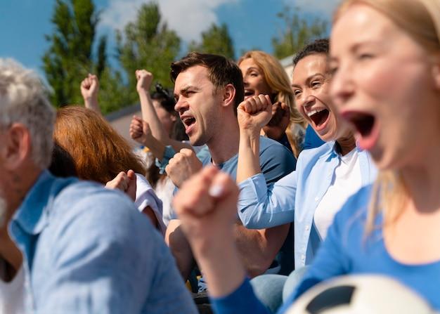 Ludzie oglądający mecz piłki nożnej w słoneczny dzień