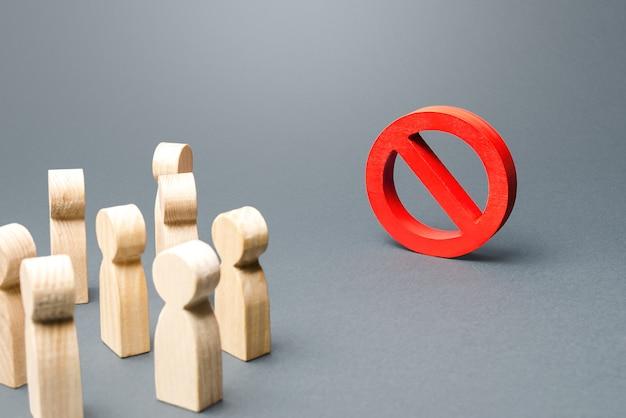 Ludzie patrzą na czerwony znak zakazu nie.