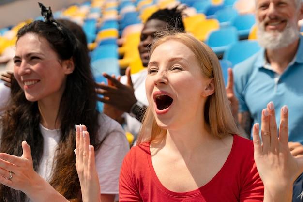 Ludzie patrzący razem na mecz piłki nożnej w słoneczny dzień