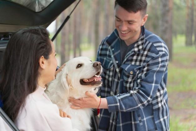 Ludzie pieszczą psa z bliska