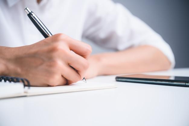 Ludzie piszą na notatniku i pracują z papierem na drewnianym stole.