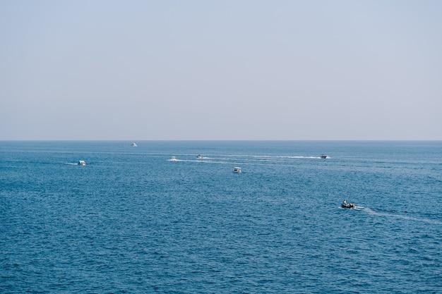 Ludzie pływają łódkami po otwartym morzu w jasny, słoneczny dzień