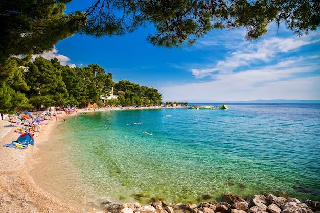 Ludzie pływający i opalający się na małej kamienistej plaży w miejscowości brela na riwierze makarskiej w chorwacji