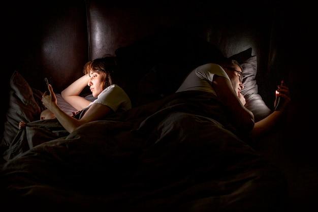 Ludzie pod dużym kątem w łóżku ze smartfonami