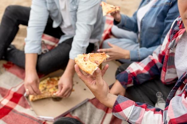 Ludzie pod wysokim kątem biorący kawałek pizzy