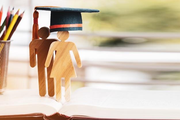 Ludzie podpisują drewno z graduation świętuje czapkę na otwartym podręczniku