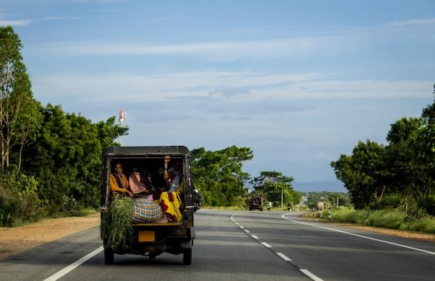 Ludzie podróżujący z tyłu napędzanego pojazdu w dół drogi w indiach