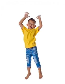 Ludzie pojęcia szczęśliwego małego azjatykciego chłopiec doskakiwania w lotniczym szczęściu, dzieciństwie, wolności w ruchu odizolowywającym na bielu
