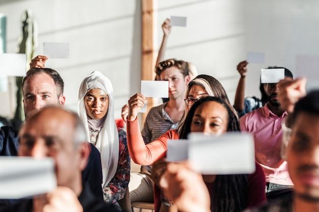 Ludzie pokazujący pustą makietę kart do głosowania