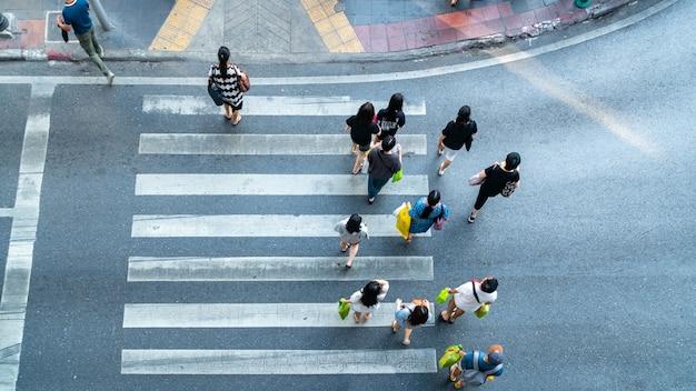 Ludzie poruszają się po przejściu dla pieszych na drodze miejskiej (w widoku z góry).