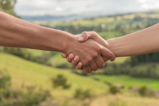 Ludzie pozdrowienia przez drżenie rąk w naturze, zachód słońca uścisk dłoni