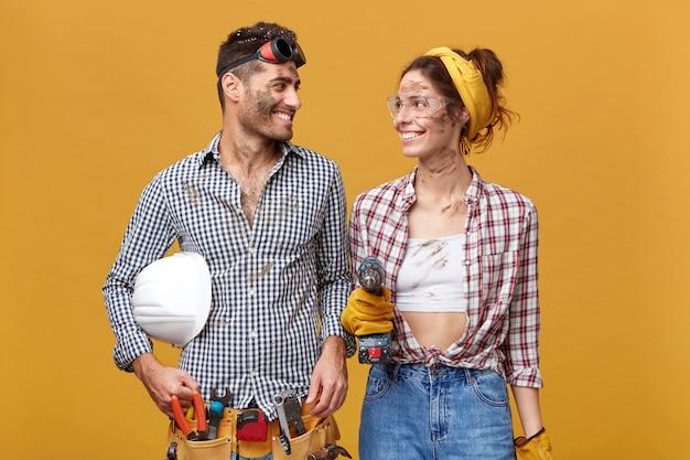 Ludzie, praca, zawód i zawód. dwóch utalentowanych, wesołych młodych rzemieślników cieszących się ze współpracy: ładna dziewczyna w okularach ochronnych z wiertłem patrząc na przystojnego kolegę i uśmiechnięta